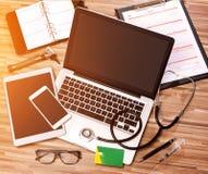 Le bureau du docteur en bois dans la définition élevée avec l'ordinateur portable, le comprimé et le MOIS Photos stock