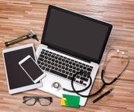 Le bureau du docteur en bois dans la définition élevée avec l'ordinateur portable, le comprimé et le MOIS Image libre de droits