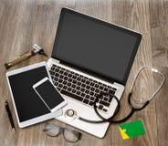 Le bureau du docteur en bois dans la définition élevée avec l'ordinateur portable, le comprimé et le MOIS Photo libre de droits