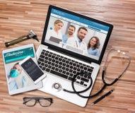 Le bureau du docteur en bois dans la définition élevée avec l'ordinateur portable, le comprimé et le MOIS Photographie stock libre de droits