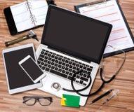 Le bureau du docteur en bois dans la définition élevée avec l'ordinateur portable, le comprimé et le MOIS Photo stock