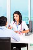Le bureau du docteur patient asiatique de consultation Photo stock