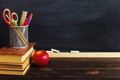 Le bureau du professeur avec des matériaux d'écriture, un livre et une pomme, un blanc pour le texte ou un fond pour un thème d'é photo stock