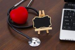 Le bureau du ` s de docteur avec l'ordinateur portable, le stéthoscope et le coeur et le bla rouges Image libre de droits