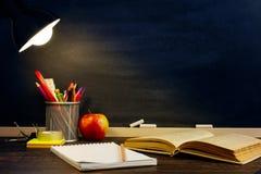 Le bureau ou un travailleur du professeur, sur lesquels les matériaux d'inscription se trouvent, un livre et une pomme, le soir s photos stock