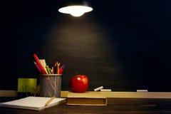 Le bureau ou un travailleur du professeur, sur lesquels les matériaux d'inscription se trouvent, un livre et une pomme, le soir s photos libres de droits