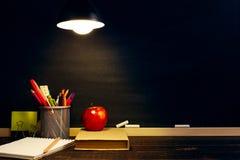 Le bureau ou un travailleur du professeur, sur lesquels les matériaux d'inscription se trouvent, un livre et une pomme, le soir s image stock