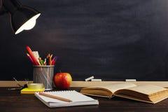 Le bureau ou un travailleur du professeur, sur lesquels les matériaux d'inscription se trouvent, un livre et une pomme, le soir s images libres de droits