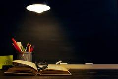 Le bureau ou un travailleur du professeur, sur lesquels les matériaux d'inscription se trouvent, livres, le soir sous la lampe Bl photos stock