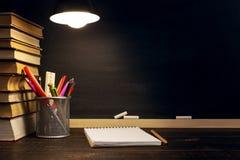 Le bureau ou un travailleur du professeur, sur lesquels les matériaux d'inscription se trouvent, livres, le soir sous la lampe Bl photo stock