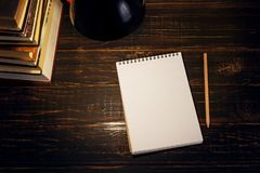 Le bureau ou un travailleur du professeur, sur lesquels les matériaux d'inscription se trouvent, livres, le soir sous la lampe Bl photographie stock