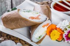 Le burrito de sushi roule avec le fromage de saumon et fondu, l'avocat et le concombre sur le plat photos stock