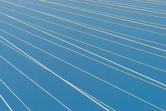 Le câble blanc de pont reste dans le modèle diagonal à travers le backgro bleu Photographie stock libre de droits