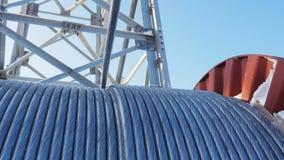 Le câble métallique déroule de la grande bobine contre le ciel clair clips vidéos
