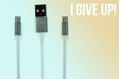 Le câble micro blanc d'usb sous forme d'homme, mains, dépeint la crainte, sur un fond modifié la tonalité l'inscription I abandon Image stock