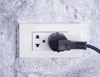 Le câble noir a branché un débouché électrique blanc monté sur W gris Photo stock
