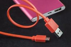 Le câble orange d'USB de couleur et la puissance rouge encaissent Photos stock