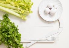 Le céleri vert frais refoule sur le plan rapproché en bois de planche à découper persil et ail de céleri cuisson de la nourriture Image stock