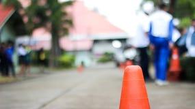 Le cône en caoutchouc sur la route est un signe de faire attention image libre de droits