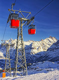 Le cabine di funivia rosse sulla ferrovia di cavo sugli sport invernali ricorrono in interruttore Immagine Stock