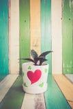 Le cactus fleurit dans le vase à coeur sur le rétro fond de vintage Image libre de droits