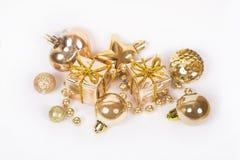 Le cadeau d'or avec d'autres babioles de Noël aiment la décoration de vacances sur le blanc Photos stock
