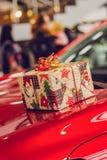 Le cadeau dans l'empaquetage lumineux se trouve sur le capot d'une voiture rouge image libre de droits