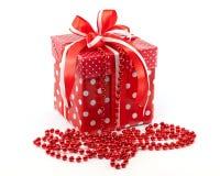Le cadeau de nouvelle année dans une boîte et une guirlande rouges Fond blanc Photos stock