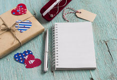Le cadeau de Saint-Valentin en papier d'emballage, chaîne des bijoux des femmes dans la poche de velours et nettoient le bloc-not Photo libre de droits