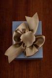 Le cadeau a emballé dans Grey Box avec le ruban sur T en bois brillant Image stock