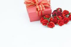 Le cadeau et les roses rouges sur le blanc ont isolé le fond Photos libres de droits