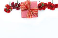 Le cadeau et les roses rouges sur le blanc ont isolé le fond Image libre de droits