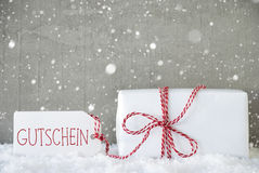 Le cadeau, fond de ciment avec des flocons de neige, Gutschein signifie le bon Photos stock