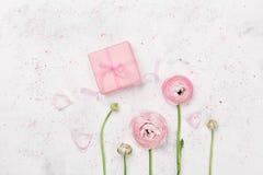 Le cadeau ou le ranunculus de boîte et beau actuel fleurissent sur la table blanche de ci-dessus pour épouser la maquette ou la c Image libre de droits