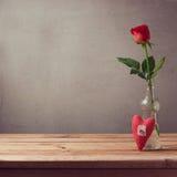 Le cadeau romantique de la fleur rose et le coeur forment sur la table en bois avec l'espace de copie Photo stock