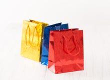 Le cadeau rouge, jaune et bleu met en sac sur le fond blanc Image stock