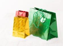 Le cadeau vert, jaune et rouge met en sac sur un fond blanc avec la neige Photos stock