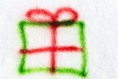 Le cadeau vert pulvérisé avec de l'aérosol peut dans la neige Photos stock