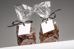 Le cadeau vide étiquette avec le ruban sur deux sacs de truffes de chocolat Photo stock