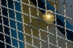 Le cadenas en forme de coeur d'amour a attaché au grillage sur un pont T Photo libre de droits