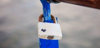 Le cadenas rouillé avec un coeur de dessin a été fermé à clef sur une balustrade épluchée Le fond de tache floue, se ferment  Photographie stock libre de droits