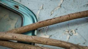 Le cadre abandonné de fenêtre de voiture avec des rondins en bois sèchent des branches d'arbre dessus photo libre de droits