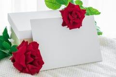 Le cadre blanc vide avec le boîte-cadeau et la rose de rouge fleurit sur tricoté Photographie stock
