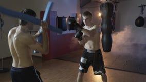 Le cadre cultivé, les trains de boxeur avec son entraîneur, accomplit la vitesse et l'exactitude de l'impact Gymnase de boxe, for banque de vidéos
