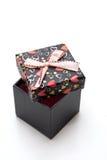Le cadre de cadeau noir fabriqué à la main ouvert avec des coeurs forment Images stock