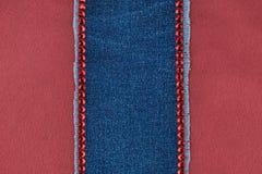 Le cadre de denim marqueté avec des fausses pierres rouges se repose sur la soie rouge Images stock