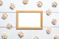 Le cadre de photo avec des roses au-dessus de blanc a peint le fond Photos libres de droits