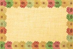Le cadre de vintage avec des fleurs de dahlia et le vieux tissu orange donnent à rétro une consistance rugueuse Images libres de droits