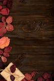 Le cadre plat de configuration du cramoisi d'automne part et des boîte-cadeau sur une obscurité photographie stock