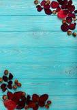 Le cadre plat de configuration du cramoisi d'automne part et des noix sur un en bois Photographie stock